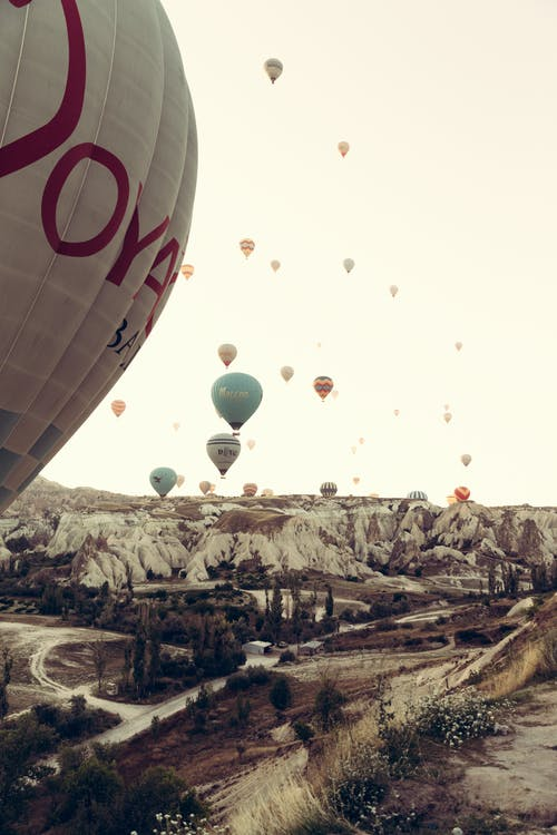 Hot air balloons flying over rocky terrain