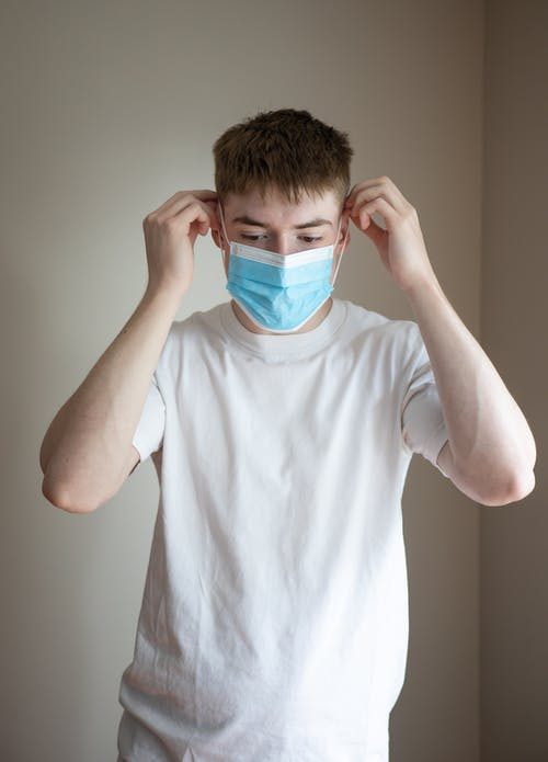 Young man putting on medical face mask