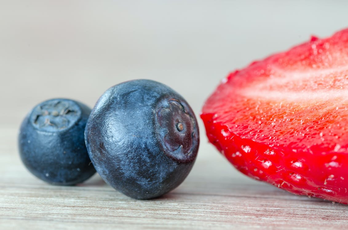 Strawberry Beside Two Blueberries
