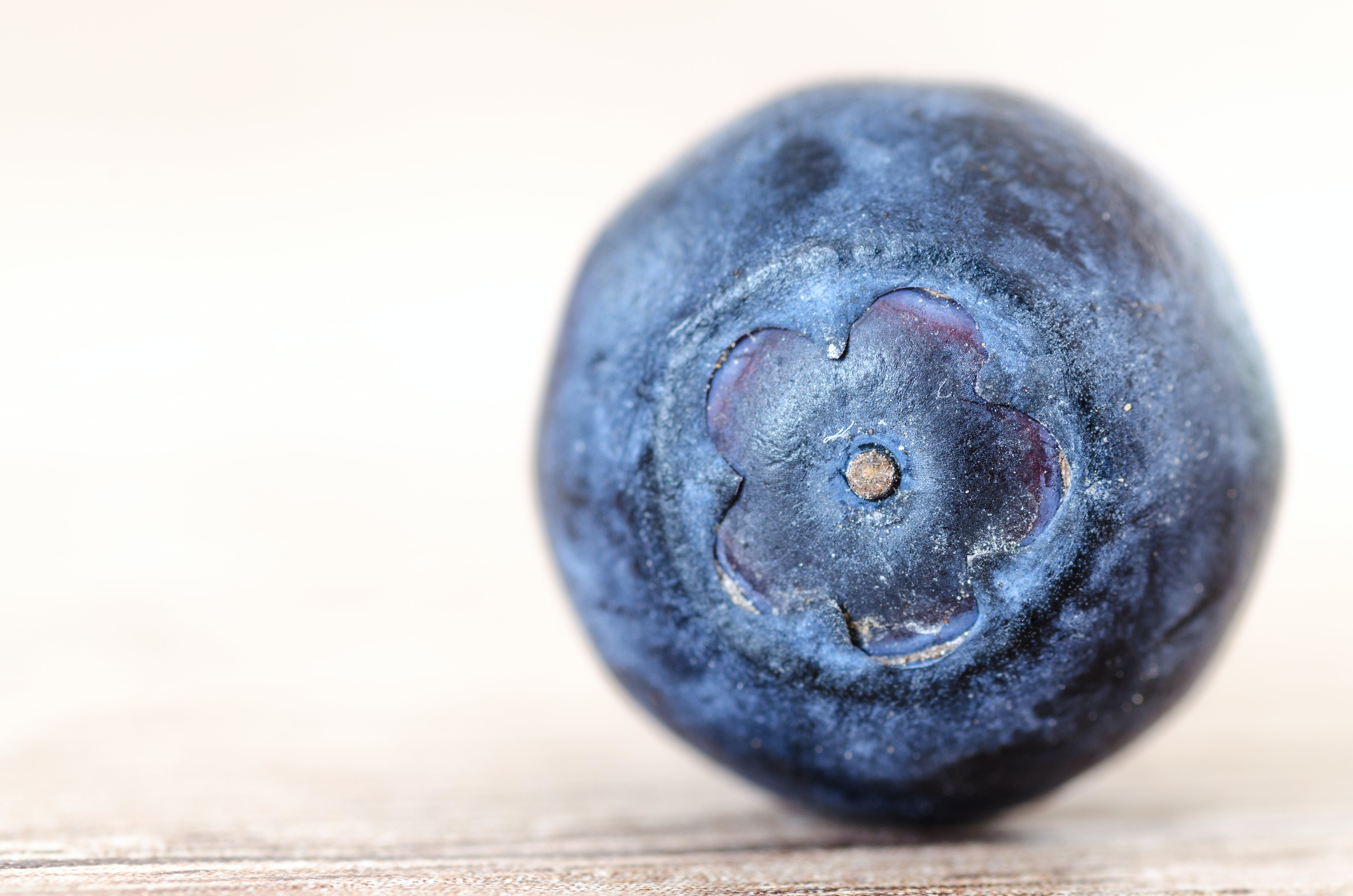 Blueberry Placed on Brown Surface