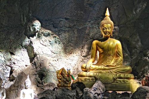 Statue of Buddha sitting in lotus pose placed inside stony cave enlightened with sun