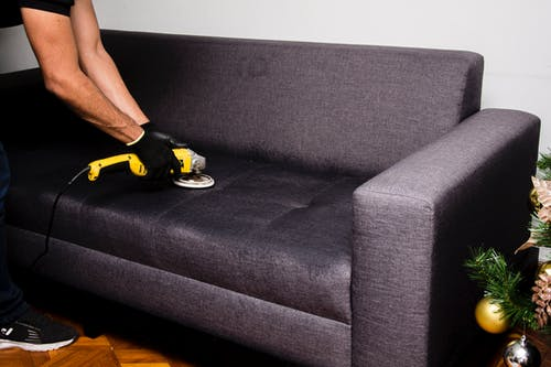 Person in Black and Yellow Shirt Lying on Gray Couch