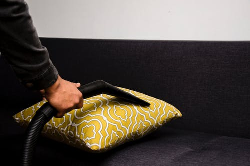 Person Holding Black and Yellow Floral Throw Pillow