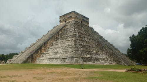 Scenery of antique stone pyramid Chichen Itza of Maya civilization located on green meadow in Mexico