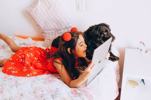 Happy girl using tablet and lying on bed with Spaniel