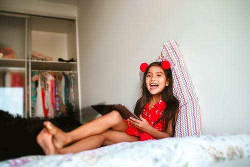 Laughing girl using tablet on bed
