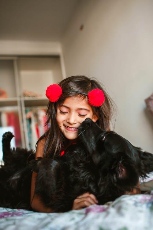 Joyful girl cuddling with funny black Spaniel on bed