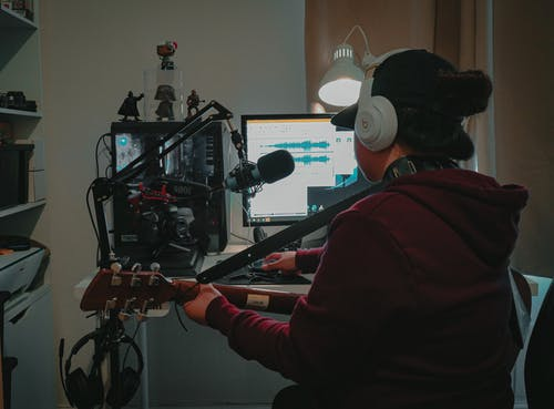 Back view faceless musician with guitar in casual wear and headphones sitting at table with computer and microphone while recording music