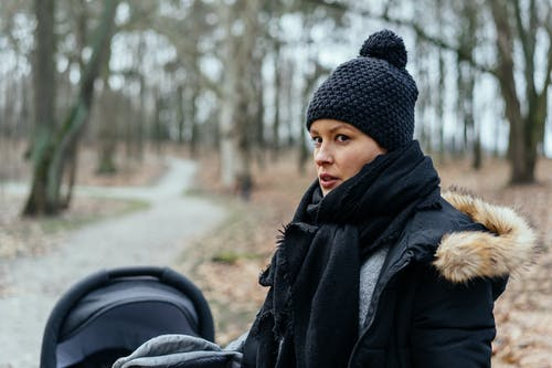 Woman in Black Knit Cap and Black Coat Standing on Road