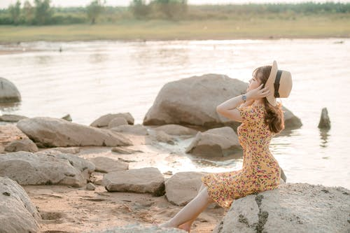 Side view slim serene female in stylish summer dress sitting on big pebble on stony riverside and putting on trendy hat