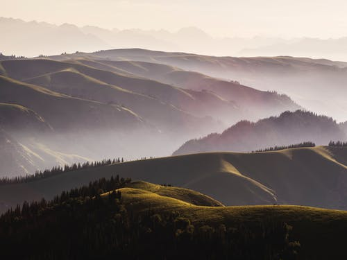 Spectacular mountains in fog under sky in evening