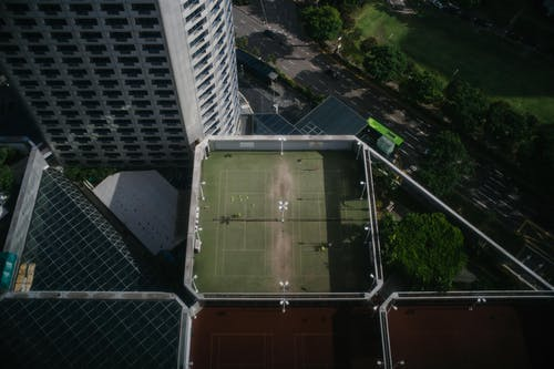 Modern skyscraper near rooftop with tennis court