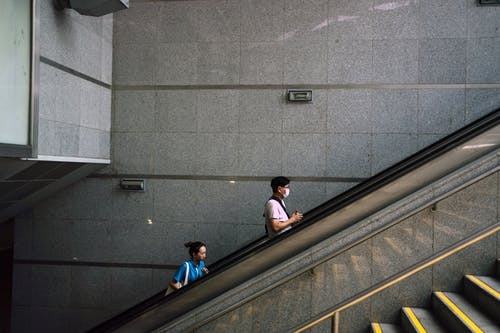 Anonymous man and woman on escalator during COVID 19 pandemic