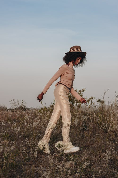 Woman in Brown Long Sleeve Shirt and White Pants Standing on Green Grass Field