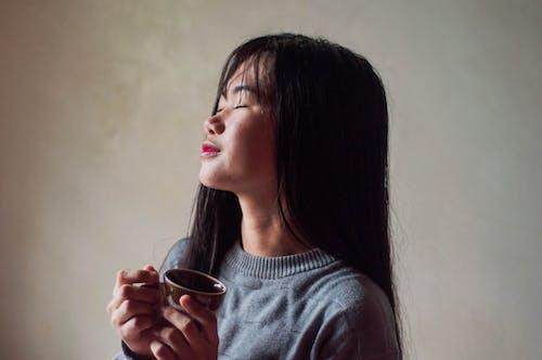 Dreamy Asian woman enjoying tea at home near wall