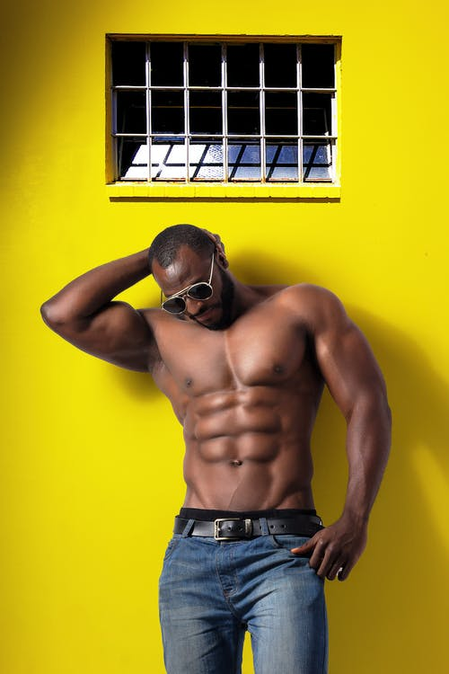 Topless Man Wearing Blue Denim Bottoms and Black Sunglasses