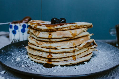 Pile of tasty homemade golden pancakes decorated with fresh blueberries and honey on plate with icing sugar