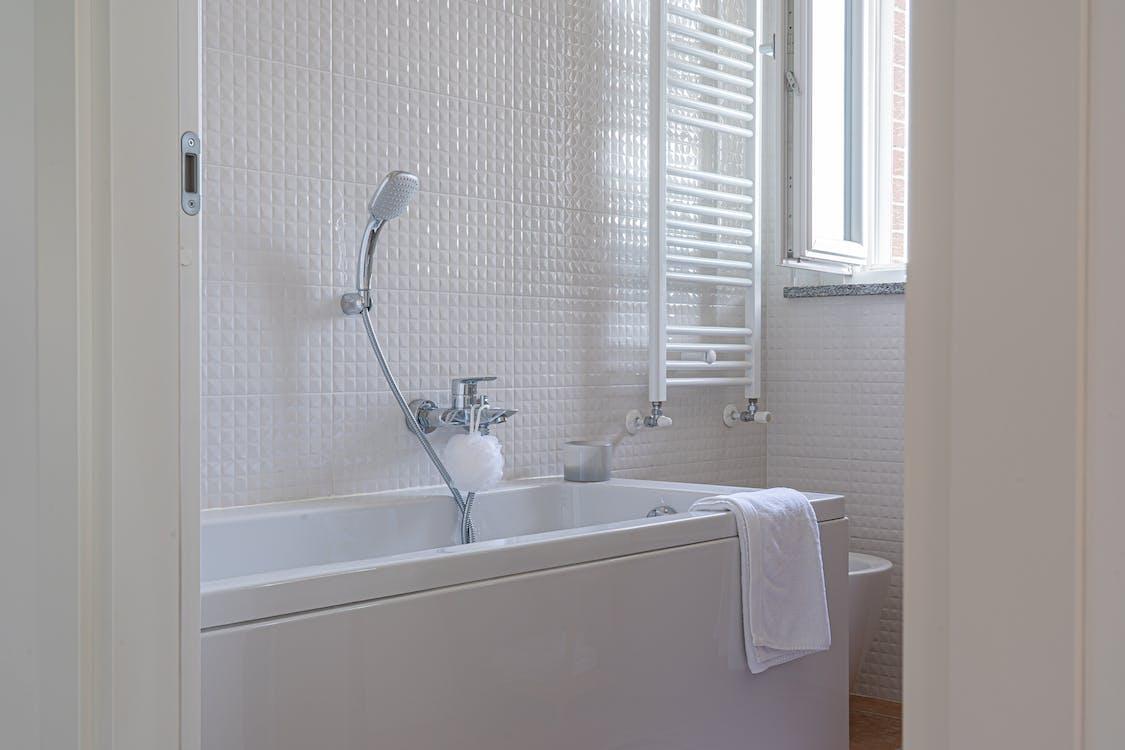 White Ceramic Bathtub Near White Shower Curtain