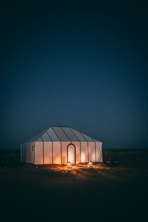 White Tent on Brown Sand during Night Time