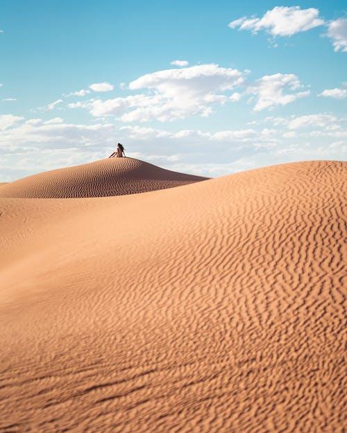 Person in Black Shirt Walking on Desert Under Blue Sky