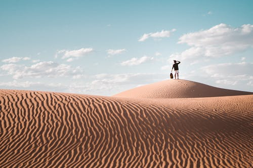 Person Standing on Brown Sand Under Blue Sky
