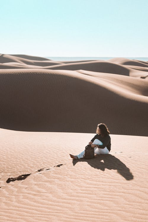Woman in White Long Sleeve Shirt Sitting on Brown Sand