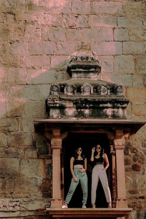 Unrecognizable stylish models on decorative porch of ancient building