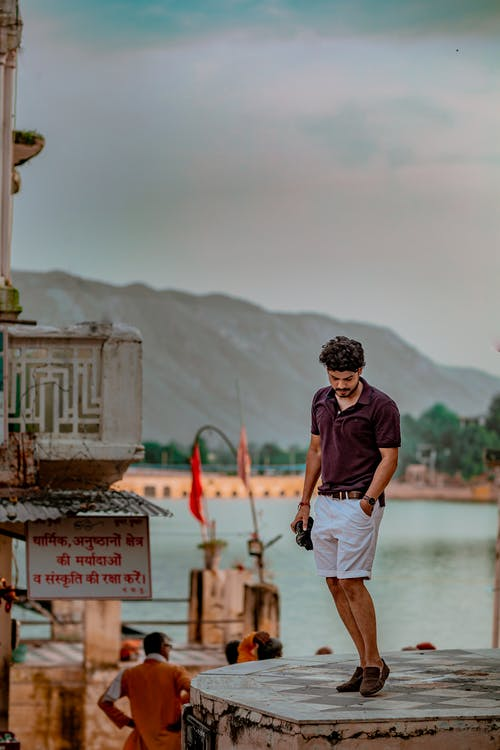 Trendy ethnic male with hand in pocket standing on cement construction behind river and mountain under cloudy sky and looking down
