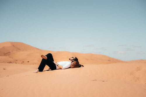Woman in Black Dress Sitting on Brown Sand