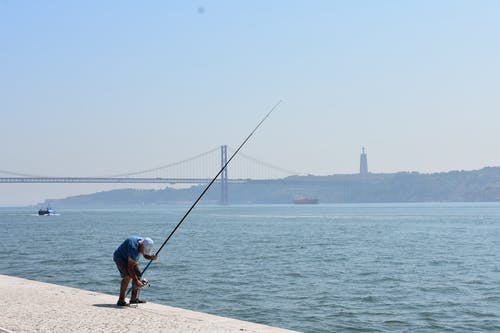 Man in Blue T-shirt and Brown Shorts Fishing on Sea