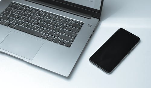 Modern laptop and smartphone on table in office