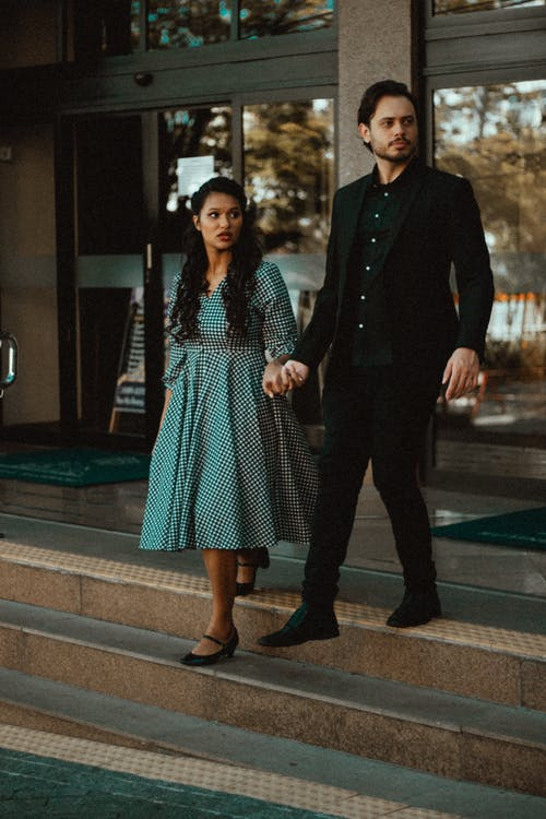Stylish ethnic couple walking down stairs while holding hands