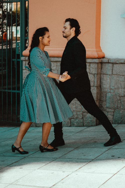 Positive ethnic couple in elegant wear dancing on pavement