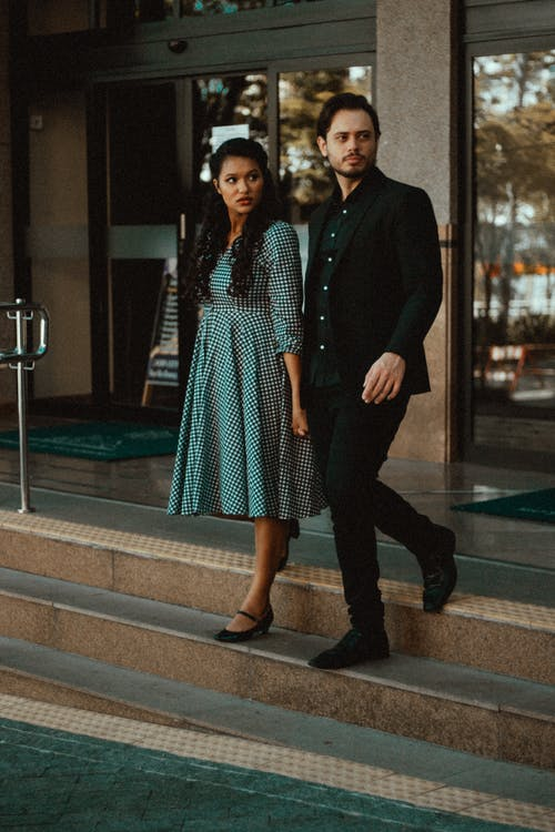 Suspicious ethnic couple strolling on staircase in town