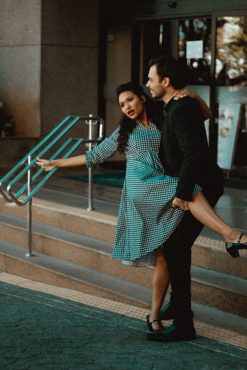 Cheerful ethnic couple embracing while dancing near stairs on street