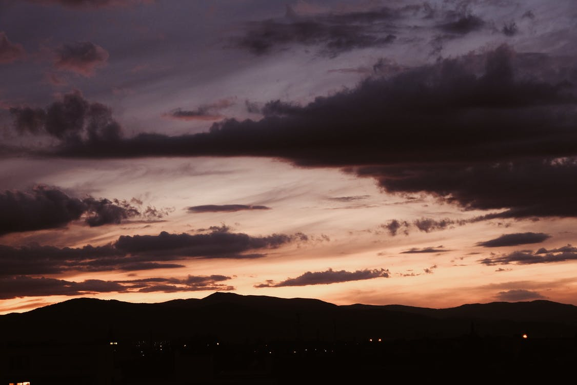 Dramatic cloudy sky at sunset above mountains in twilight