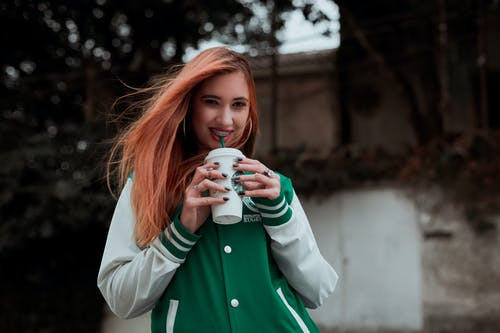 Positive young female drinking hot drink and standing on street while looking at camera