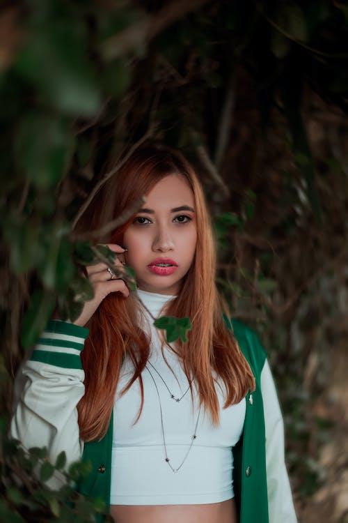 Pensive teenage girl standing near tree