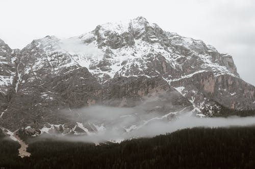 Gray clouds floating over lush coniferous forest located in snowy mountainous valley on overcast winter day