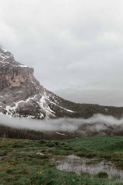 Picturesque landscape of mountain ridge covered with snow and swampy terrain under thick mist on overcast day