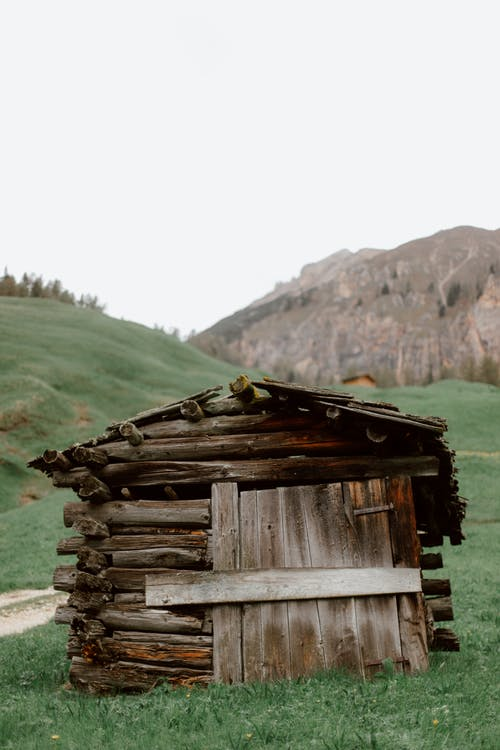 Wooden barn in green valley with mountain