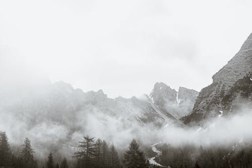 Snowy mountain peaks under thick fog and clouds