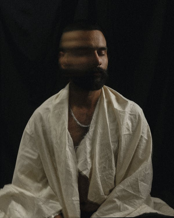 Long exposure of Asian male living with psychological disorder in white worn out robe sitting on floor and moving head against black background