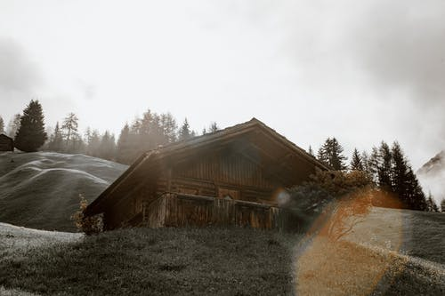 Shabby lonesome cottage on grassy hilly terrain