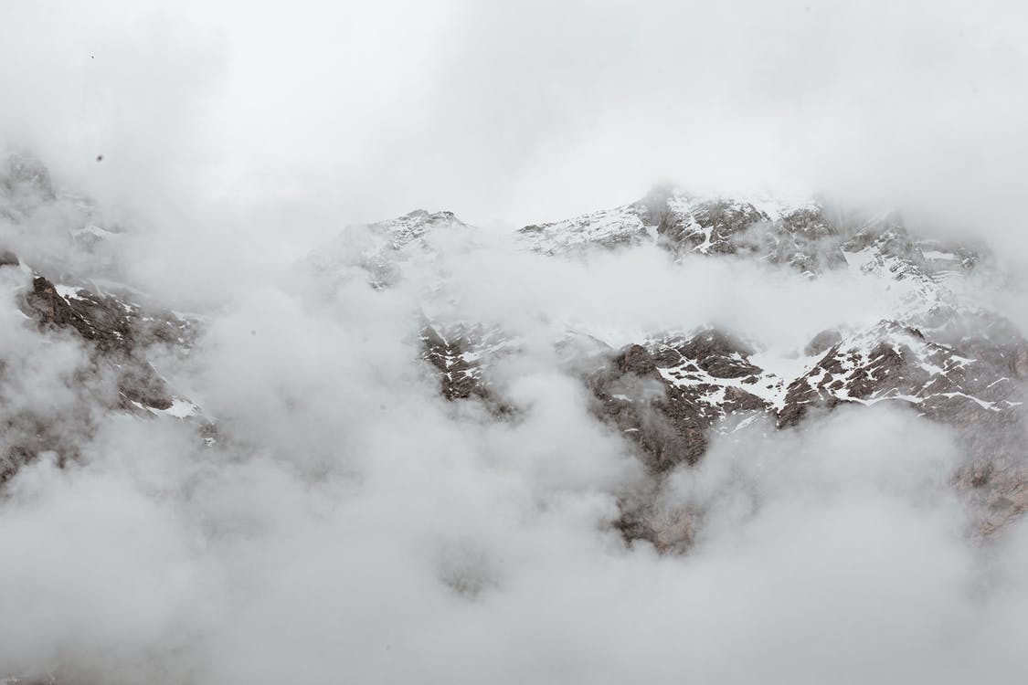 Dense fog covering massive mountain range with snowy rocky slopes on overcast day