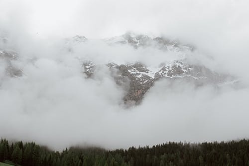 Mountain ridge in clouds with forest in front