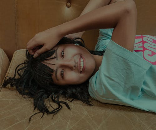 Smiling young Asian lady resting on couch