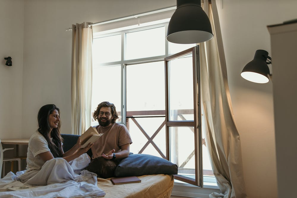Woman and man sitting on bed. | Photo: Pexels