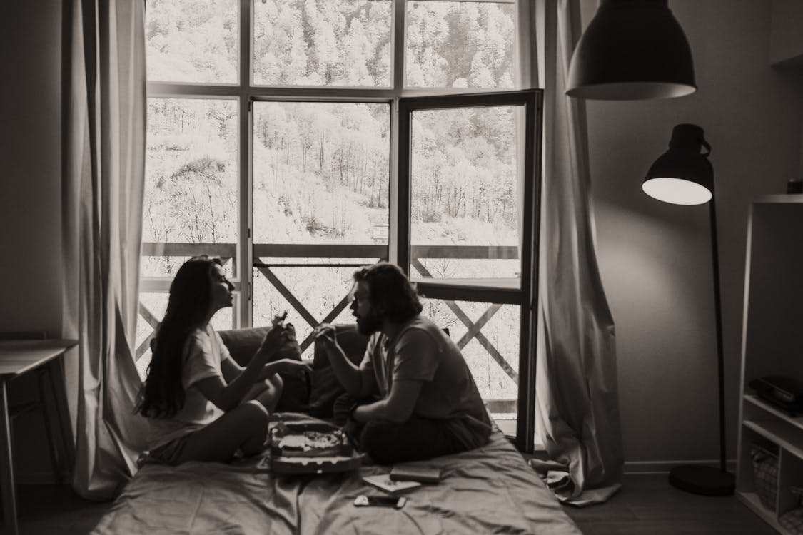 Grayscale Photo of 2 Women Sitting on Bed