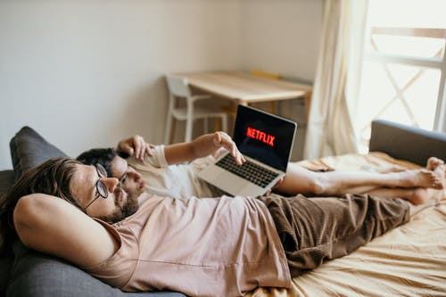 Man in White T-shirt Lying on Bed Using Macbook